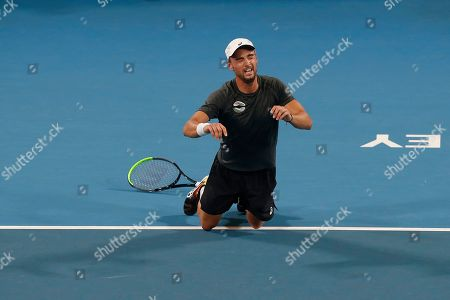 Dimitar Kuzmanov of Bulgaria reacts to winning the match point against Steve Darcis of Belgium during their ATP Cup tennis match in Sydney