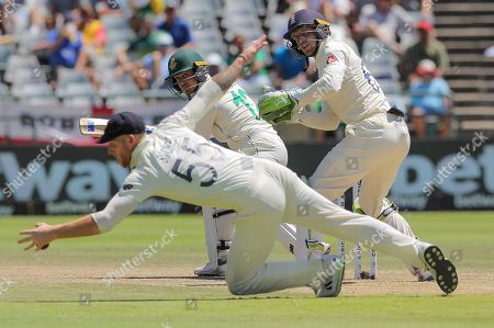 England's Ben Stokes fields the ball while England's wicketkeeper Jos Buttler and South Africa's batsman Quinton De Kock watches on during day five of the second cricket test between South Africa and England at the Newlands Cricket Stadium in Cape Town, South Africa