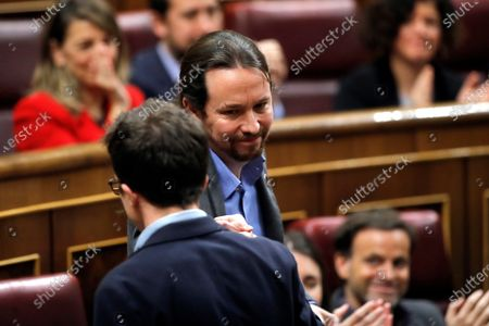 Leader of Spanish left wing Podemos party, Pablo Iglesias (R), greets former party colleague now leader of Mas Pais party (lit. More Country), Inigo Errejon (L), after his speech at the second investiture voting at the Lower House in Madrid, Spain, 07 January 2020. The Spanish Parliament holds the second investiture voting at Parliament in which acting Prime Minister Pedro Sanchez is expected to win by a tight majority.