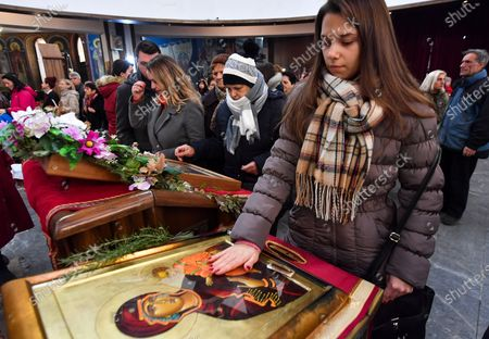 Stock Photo of A Macedonian Orthodox believer touches the icon 'Mother of God with her son' in the central Orthodox Church of Saint Clement after the Christmas mass in Skopje, Republic of North Macedonia, 07 January 2020. Orthodox Christians celebrate Christmas on 07 January according to the Julian calendar.