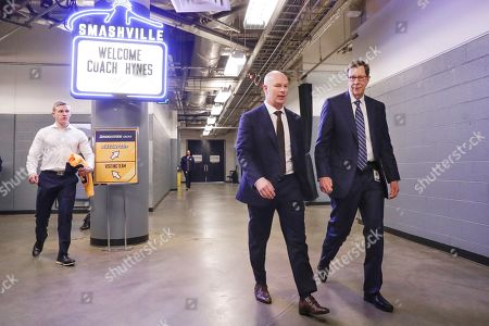 New Nashville Predators head coach John Hynes, second from right, walks to a news conference with Predators general manager David Poile, right,, in Nashville, Tenn. The Predators hired Hynes, the former New Jersey Devils coach, as the third coach in franchise history after firing Peter Laviolette