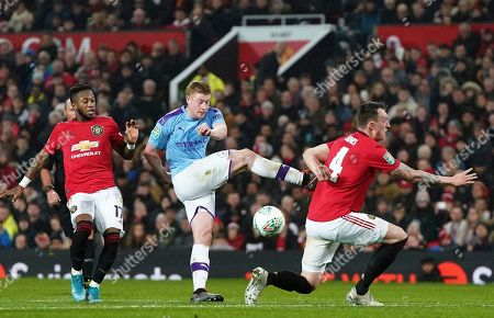 Manchester City's Kevin De Bruyne, centre attempts a shot on goal, which is blocked by Manchester United's Phil Jones, right, during the English League Cup semifinal first leg soccer match between Manchester United and Manchester City and at Old Trafford, Manchester, England
