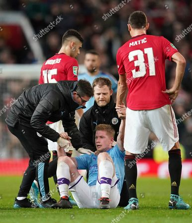 Manchester City's Kevin De Bruyne is helped to his feet after an accidental clash with Manchester United's Victor Lindelof during the English League Cup semifinal first leg soccer match between Manchester United and Manchester City and at Old Trafford, Manchester, England