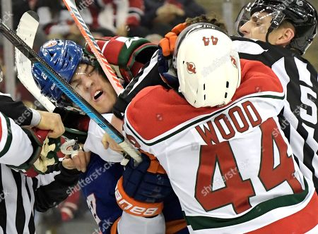 New Jersey Devils left wing Miles Wood (44) fights with New York Islanders left wing Anders Lee (27) during the first period of an NHL hockey game, in Newark, N.J