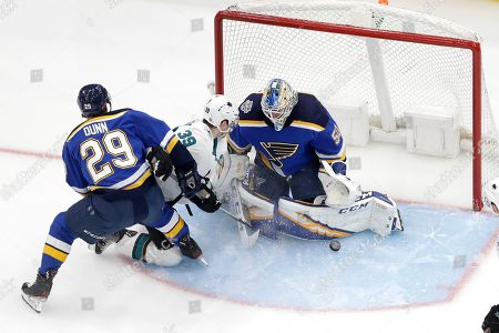 Stock Photo of St. Louis Blues goaltender Jordan Binnington (50) deflects the puck as Blues' Vince Dunn (29) and San Jose Sharks' Logan Couture (39) watch during the second period of an NHL hockey game, in St. Louis