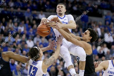 Jeremiah Robinson-Earl, Christian Bishop, Marcus Zegarowski. Creighton's Christian Bishop (13) and Marcus Zegarowski, center, and Villanova's Jeremiah Robinson-Earl (24) go for a rebound during the first half of an NCAA college basketball game in Omaha, Neb