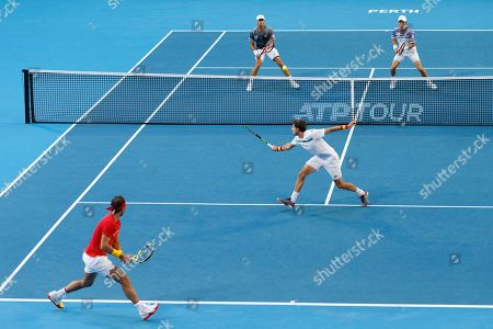 Rafael Nadal, Pablo Carreno Busta. Pablo Carreno Busta, bottom right, lunges as Spanish team mate Rafael Nadal, bottom left, watches in their doubles match against Japan's Ben McLachlan, top left, and Go Soeda at the ATP Cup in Perth, Australia