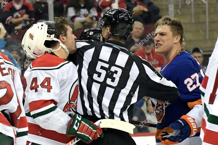 Stock Image of New Jersey Devils left wing Miles Wood (44) and New York Islanders left wing Anders Lee (27) are separated by linesman Bevan Mills (53) during the first period of an NHL hockey game, in Newark, N.J
