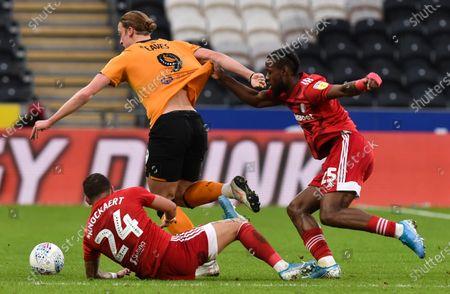 Tom Eaves of Hull City holds off Anthony Knockaert and Joshua Onomah of Fulham