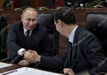 President Bashar al-Assad (R) shaking hands with his Russian counterpart Vladimir Putin at the headquarters of the Russian forces in the Syrian capital Damascus. Putin met his Syrian counterpart Bashar al-Assad during an unprecedented visit to Damascus as the prospect of war between Iran and the United States loomed over the region.
