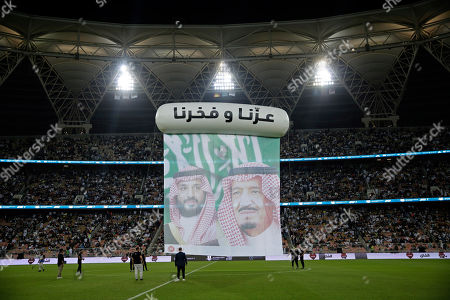 "A banner is displayed on the pitch with pictures of Saudi King Salman, right, and Crown Prince Mohammed bin Salman, during halftime of the Spanish Super Cup semifinal soccer match between Real Madrid and Valencia at King Abdullah stadium in Jiddah, Saudi Arabia, . Words read in Arabic, ""Our pride and proud"