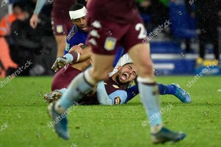 Aston Villa's Douglas Luiz, center, grimaces in pain after clashing with Leicester's Ricardo Pereira, top, during the English League Cup semifinal first leg soccer match between Leicester City and Aston Villa at the King Power Stadium in Leicester, England