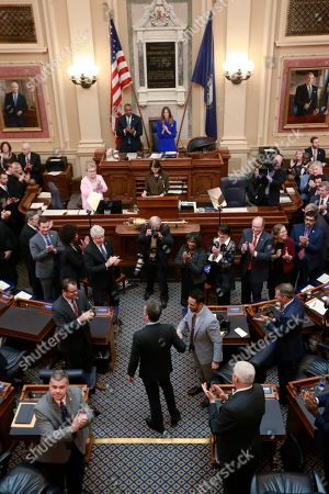 Virginia Gov. Ralph Northam, bottom center, arrives in the House to deliver his State of the Commonwealth address before a joint session of the Assembly at the state Capitol in Richmond, Va