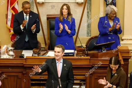 Virginia Gov. Ralph Northam, bottom, prepares to deliver his State of the Commonwealth address as House speaker, Eileen Filler-Corn, D-Farifax, top center, Lt. gov. Justin Fairfax, top left, and Senate President Pro tem, Louise Lucas, D-Portsmouth, right, applaud before a joint session of the Virginia Assembly at the Virginia state Capitol in Richmond, Va