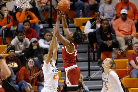 Madi Williams, Lauren Fields, Abbie Winchester. Oklahoma guard Madi Williams shoots between Oklahoma State guard Lauren Fields, left, and guard Madi Williams during the second half of an NCAA college basketball game in Stillwater, Okla