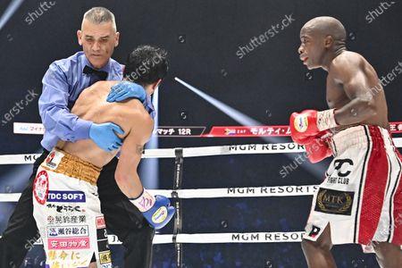 Japan's Akira Yaegashi (C) reacts after losing against South Africa's Moruti Mthalane (R) at the 9th round during the IBF flyweight title boxing bout at Yokohama Arena