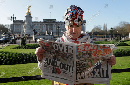 "Self-proclaimed royal super-fan John Loughrey poses for the media backdropped by Buckingham Palace in London, . In a statement Prince Harry and his wife, Meghan, said they are planning ""to step back"" as senior members of the royal family and ""work to become financially independent"