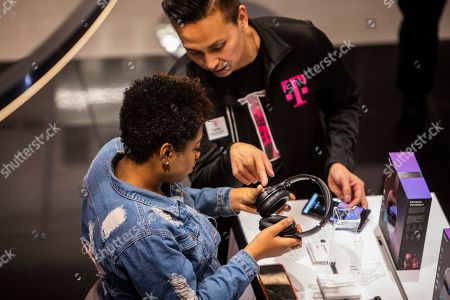 IMAGE DISTRIBUTED FOR T-MOBILE - Guests try out SVN Neon 100 headphones during the Steve Aoki SVN launch event at the T-Mobile Strip store on in Las Vegas