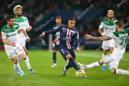 PSG's forward Kylian Mbappe dribbles past Saint-Etienne's Yohan Cabaye and Mathieu Debuchy (L)