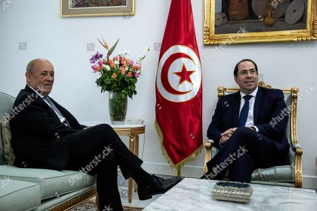 Tunisian Prime minister Youssef Chahed, right, speaks with French Foreign Minister Jean-Yves Le Drian, in Tunis, Tunisia