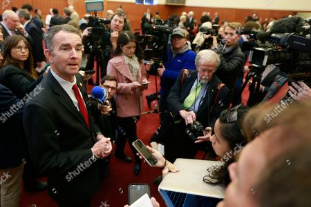 Stock Picture of Virginia Gov. Ralph Northam, left, speaks to the medial after a news conference at the Virginia State Capitol in Richmond, Va., . Northam announced several bills related to Confederate statues as well as issues related to historic African American cemeteries