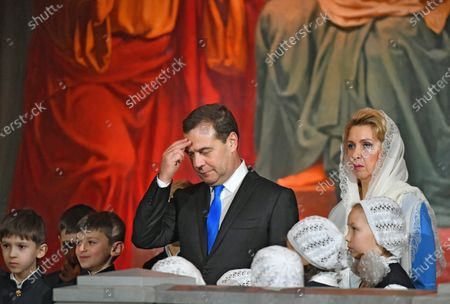 Stock Picture of Christmas mass in the Cathedral of Christ the Savior. Russian Prime Minister Dmitry Medvedev (center) and his wife Svetlana Medvedeva (right) attend the mass