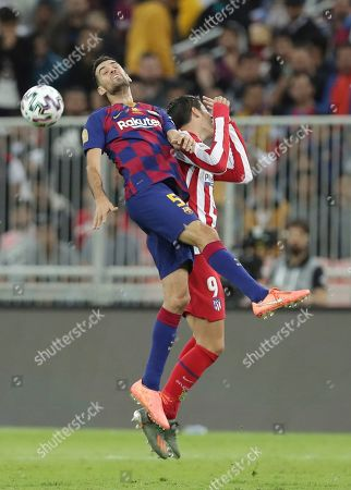 Barcelona's Sergio Busquets, left, vies for the ball with Atletico Madrid's Alvaro Morata during the Spanish Super Cup semifinal soccer match between Barcelona and Atletico Madrid at King Abdullah II stadium in Jiddah, Saudi Arabia