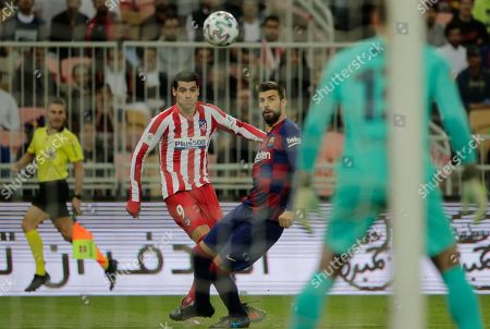 Atletico Madrid's Alvaro Morata, left, shoots the ball as Barcelona's Gerard Pique looks, during the Spanish Super Cup semifinal soccer match between Barcelona and Atletico Madrid at King Abdullah II stadium in Jiddah, Saudi Arabia