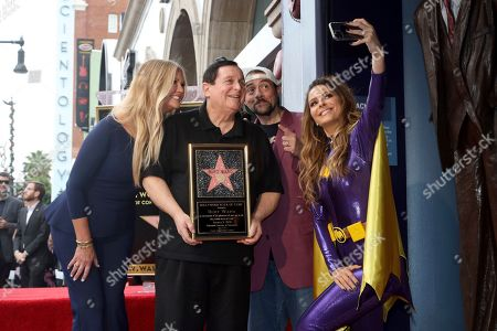 """Nancy O'Dell, Burt Ward, Kevin Smith, Maria Menounos. Burt Ward, who portrayed Dick Grayson and his alter ego Robin in the 1960's TV series """"Batman,"""" second left, poses with TV host Nancy O'Dell, left, filmmaker and comic book enthusiast Kevin Smith and TV personality Maria Menounos, right, take a selfie following a ceremony honoring Ward with a star on the Hollywood Walk of Fame in Los Angeles on"""