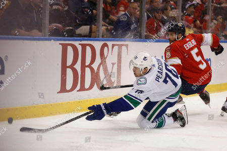 Vancouver Canucks left wing Tanner Pearson (70) and Florida Panthers defenseman Aaron Ekblad (5) trip going for the puck during the period of an NHL hockey game against the, in Sunrise, Fla