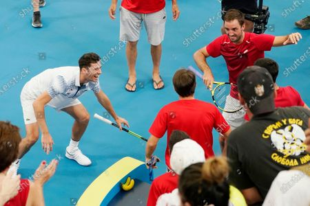 Viktor Troicki (R) and Nikola Cacic (L) of Serbia celebrate their win with team mates over Peter Polansky and Adil Shamasdin of Canada during day eight of the ATP Cup tennis tournament at Ken Rosewall Arena in Sydney, Australia, 10 January 2020.