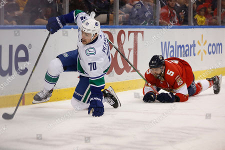 Nick Bjugstad, Tanner Pearson, Aaron Ekblad. Vancouver Canucks left wing Tanner Pearson (70) and Florida Panthers defenseman Aaron Ekblad (5) trip while going for the puck during the period of an NHL hockey game, in Sunrise, Fla