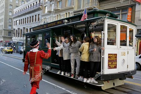 """A group of girls riding a Powell Street cable car are greeted by Beefeater doorman Tom Sweeney outside the Sir Francis Drake Hotel in San Francisco. Another bit of old, quirky San Francisco will be no more when Tom Sweeney finally hangs up his white pressed collar and signature Beefeater jacket after more than four decades as chief doorman at downtown's Sir Francis Drake Hotel. Sweeney has opened doors for movie stars and shaken hands with every U.S. president since Gerald Ford, with the exception of Donald Trump. He's taken photos with countless visitors from around the world, often after telling them where to catch the cable car and how to get to Fisherman's Wharf. The man known as a """"San Francisco original"""" and """"living landmark"""" retires Sunday, Jan. 12, 2020, after 43 years"""