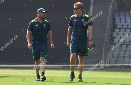 Andrew McDonald, Aaron Finch. Australian cricket captain Aaron Finch, left, along with coach Andrew McDonald examines the pitch, before addressing a press conference ahead of their 3-match one-day international series against India in Mumbai, India