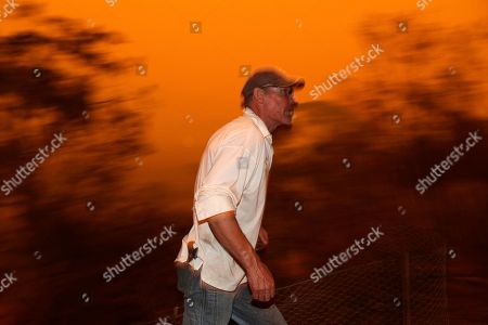 Evan Harris rushes around his property preparing to minimize fire impact at Burragate, Australia, as a nearby fire threatens the area. Thousands of people are fleeing their homes and helicopters are dropping supplies to towns at risk of wildfires as hot, windy conditions threaten already fire-ravaged southeastern Australian communities. The danger is centered on Australia's most populous states, including coastal towns that lost homes in earlier fires