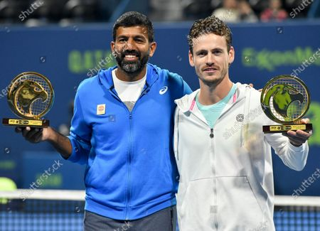 Stock Photo of Wesley Koolhof of the Netherlands (R) and Rohan Bopanna  of India pose with their trophies after winning the doubles final match against Luke Bambridge  of Britain and Santiago Gonzalez Mexico at the ATP Qatar Open Tennis tournament in Doha, Qatar, 10 January 2020.
