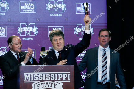 Stock Picture of Mark Keenum, Mike Leach, John Cohen. New Mississippi State NCAA college football coach Mike Leach, center, stands between university president Mark Keenum, left, and athletic director John Cohen, as he rings the symbolic cowbell before reporters and school supporters, at the Starkville, Miss., based university, after being officially introduced as the head coach