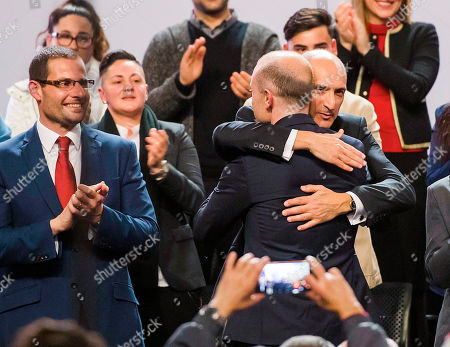 Maltese Prime Minister and Labour Party leader Joseph Muscat, back to camera at right, is hugged by party member Chris Fearne during a party general assembly where he delivered his farewell speech as party leader in Kordin, near Valletta, . At left party member Robert Abela. A new leader will be elected during the weekend