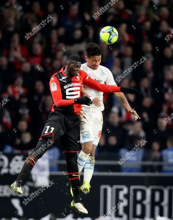 Rennes' M'Baye Niang, left, jumps for the ball with Marseille's Boubacar Kamara during the League One soccer match between Rennes and Marseille, at the Roazhon Park stadium in Rennes, France