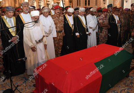 In this photo made available by Oman News Agency, Oman's new sultan Haitham bin Tariq Al Said, second from left of second row, attends the prayer ceremony for Sultan Qaboos' coffin at Sultan Qaboos Grand Mosque in Muscat, Oman, . Sultan Qaboos bin Said, the Mideast's longest-ruling monarch who seized power in a 1970 palace coup and pulled his Arabian sultanate into modernity while carefully balancing diplomatic ties between adversaries Iran and the U.S., has died. He was 79