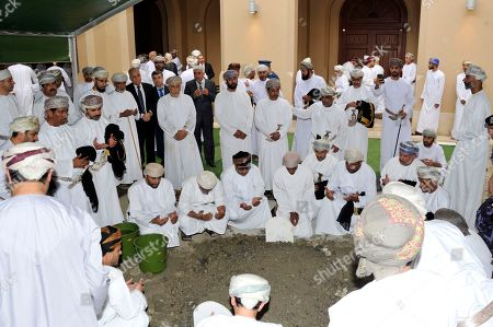 In this photo made available by Oman News Agency, Omani officials pray over the grave of Sultan Qaboos after his burial in Muscat, Oman, . Sultan Qaboos bin Said, the Mideast's longest-ruling monarch who seized power in a 1970 palace coup and pulled his Arabian sultanate into modernity while carefully balancing diplomatic ties between adversaries Iran and the U.S., has died. He was 79