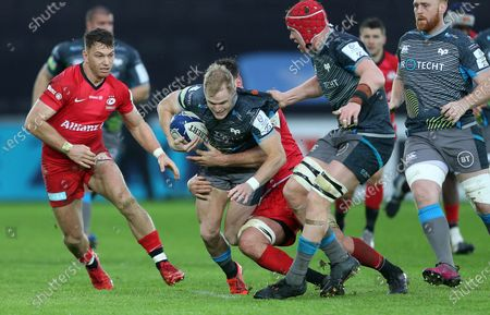 Stock Image of Aled Davies of Ospreys is tackled by Calum Clark of Saracens.