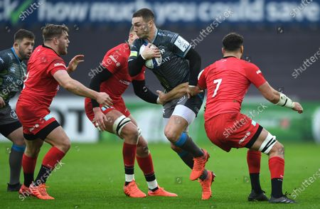 George North of Ospreys is tackled by Jack Singleton and Calum Clark of Saracens.