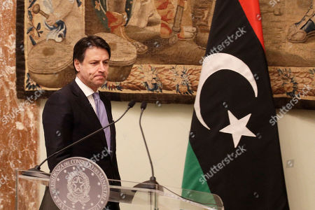 Italian Premier Giuseppe Conte walks past a Libyan flag at the end of his meeting with Libya's Prime Minister Fayez al-Sarraj at Chigi palace, in Rome