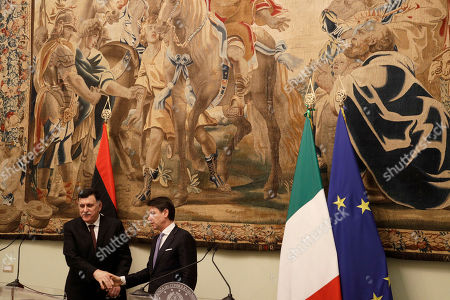 Libya's Prime Minister Fayez al-Sarraj, left, shakes hands with Italian Premier Giuseppe Conte after their meeting at Chigi palace, in Rome