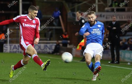Dan Butler of Peterborough United puts a cross in beyond Stuart O'Keefe of Gillingham