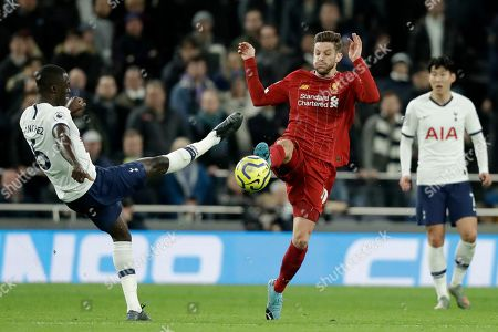 Stock Photo of Tottenham's Davinson Sanchez, left, vies for the ball with Liverpool's Adam Lallana during the English Premier League soccer match between Tottenham Hotspur and Liverpool at the Tottenham Hotspur Stadium in London, England