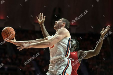 Illinois' Giorgi Bezhanishvili (15) goes to the basket as Rutgers' Shaq carter defends in the first half of an NCAA college basketball game, in Champaign, Ill