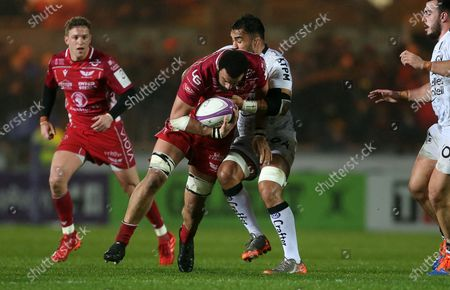 Uzair Cassiem of Scarlets is tackled by Liam Messam of Toloun.