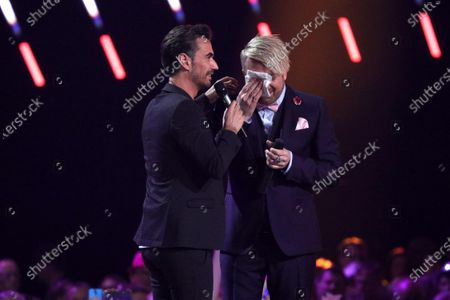 Ross Antony (R) cries on stage next to Florian Silbereisen (L)  during the TV show 'Schlagerchampions 2020 - Das grosse Fest der Besten' (lit. The Big Festival of the Best) in Berlin, Germany, 11 January 2020.